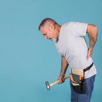 Heimwerker, der unter der rückenschmerzholding den hammer stehen gegen blauen hintergrund leidet