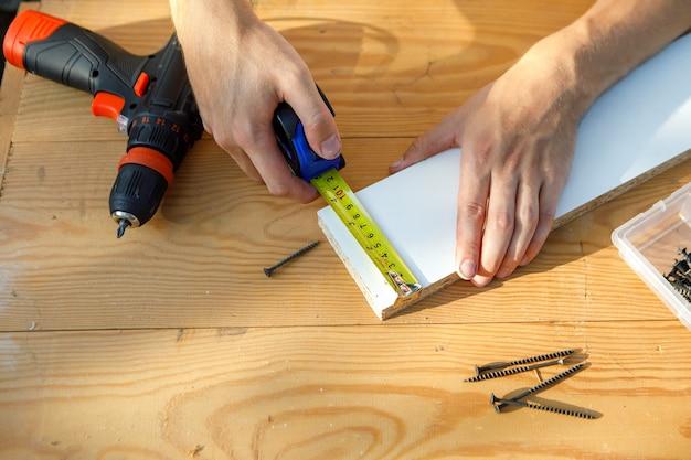 Heimwerker in blauer uniform arbeitet mit automatischem schraubendreher der elektrizität. konzept der hausrenovierung.