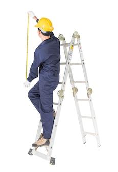 Heimwerker in der uniform, die auf leiter bei der anwendung des maßbands auf weiß steht