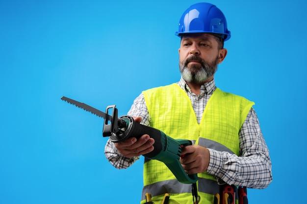 Heimwerker in uniform mit säge vor blauem hintergrund