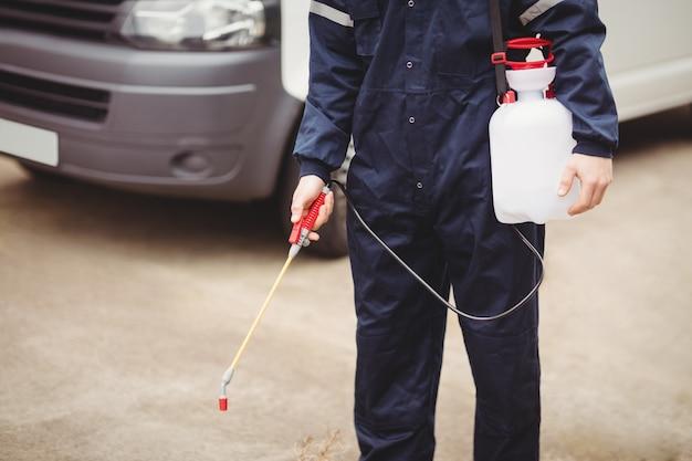 Heimwerker mit dem insektizid, das vor seinem packwagen steht