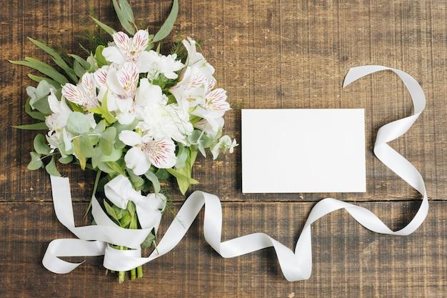 Heiratender blumenstrauß der weißen karte und der peruanischen lilie gebunden mit band auf hölzernem schreibtisch