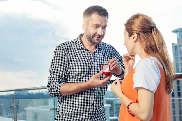 Heiratsantrag. glücklicher gutaussehender mann, der sein herz anbietet, während er seiner freundin vorschlägt, ihn zu heiraten