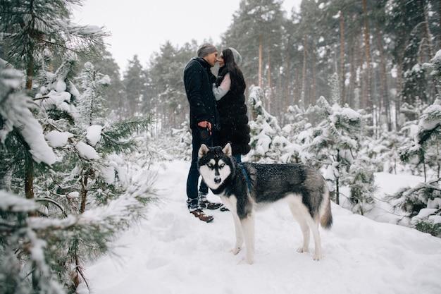 Heiserer hund und küssende paare in der liebe, die in wald des verschneiten winters am kalten wintertag geht