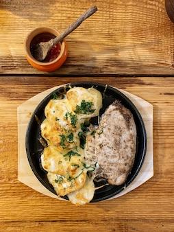 Heiß gebackenes hähnchen mit kartoffeln und käse in rustikaler draufsicht