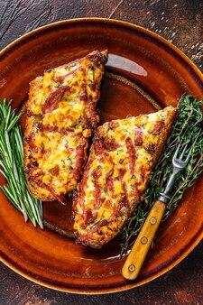 Heiß gebackenes sandwich auf baguettebrot mit schinken, speck, gemüse und käse auf einem rustikalen teller