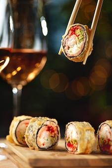 Heiß gebratene sushi-rolle mit lachs und wein. sushi-menü. japanisches essen. heiß gebratene sushi-rolle