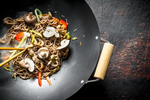Heiße asiatische soba-nudeln mit gemüse, pilzen und sauce. auf rustikaler oberfläche