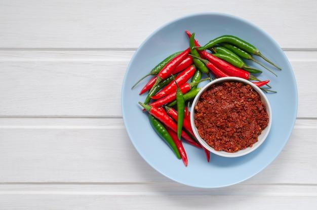 Heiße chilipfeffersauce paste harissa, traditionelle tunesien, marokkaner, arabische küche adjika, chilipfeffergewürze und frische rote und grüne chilischoten in blauem teller, über weißem hintergrund. nahansicht