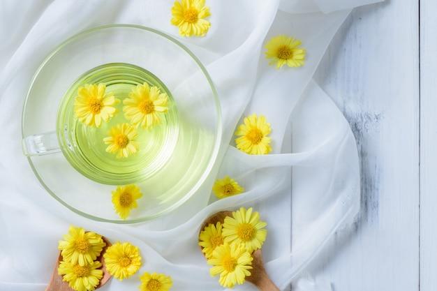 Heiße chrysantheme in einer tasse auf einem weißen tuch und weißem holz