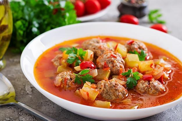 Heiße eintopfgerichttomatensuppe mit fleischklöschen und gemüsenahaufnahme in einer schüssel auf dem tisch. albondigas suppe, spanisches und mexikanisches essen.