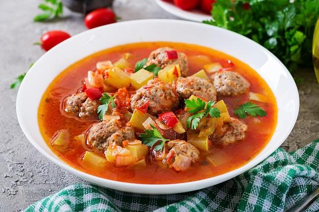 Heiße eintopftomatesuppe mit fleischklöschen und gemüsenahaufnahme in einer schüssel auf dem tisch. albondigas suppe