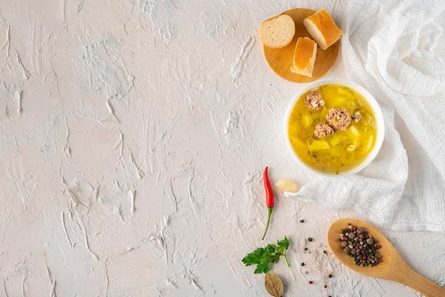 Heiße frische gekochte suppe mit fleischklöschen und kartoffel mit brot auf einer weißen tabelle, geschmackvolle abendessen