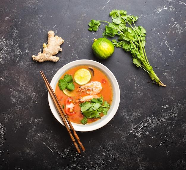 Heiße frische würzige traditionelle thailändische suppe tom yum mit garnelen, limette, koriander in einer schüssel auf rustikalem schwarzem steinhintergrund