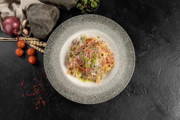 Heiße gekochte tagliatelle-nudeln mit parmaschinken, parmesan und kräutern
