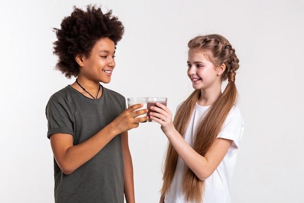 Heiße getränke halten. fröhliche, ansprechende kinder, die mit süßen getränken gefüllte gläser anstoßen, während sie sich ansehen