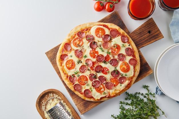 Heiße hausgemachte italienische peperoni-pizza mit salami, mozzarella auf weißem tisch
