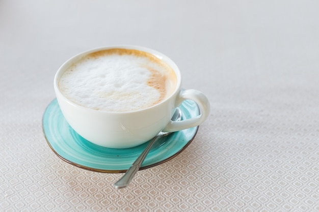 Heiße kaffee-cappuccino-latte-kunst in der jadefarbschale lokalisiert auf beigem tisch. draufsicht auf cappuccino-kaffeetasse. latte-kunst auf milchigem schaum. heißes italienisches energetisierendes getränk, das im grünen keramikbecher serviert wird