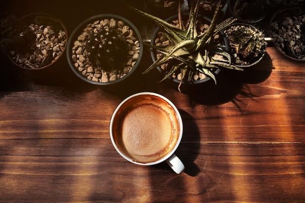 Heiße kaffee latte-schale auf holztisch darunter mit natürlichem licht.