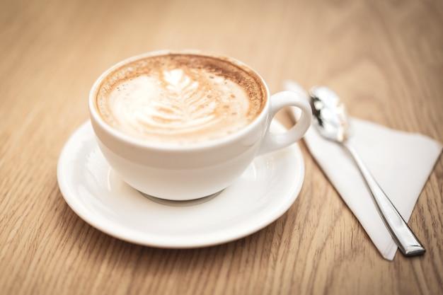 Heiße kaffeecappuccino lattekunst auf hölzernem hintergrund