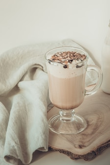 Heiße kaffeelatte mit dickem schaum und geriebener schokolade