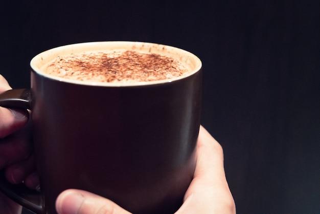 Heiße kaffeetasse auf dem frauenhand-, lebensmittel- und getränkkonzept