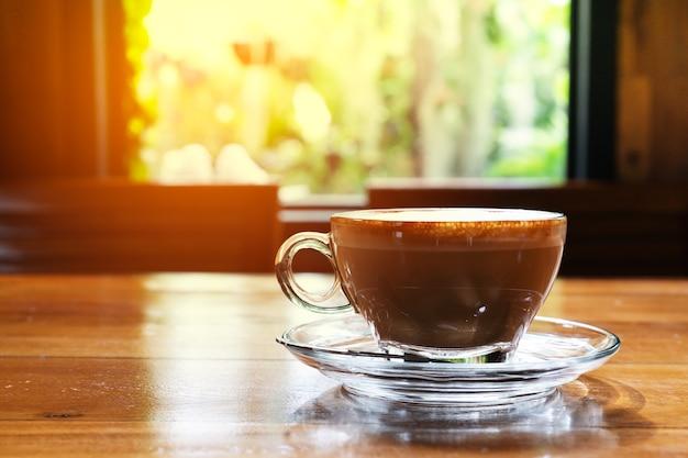 Heiße kaffeetasse auf dem holztisch, fensteransicht