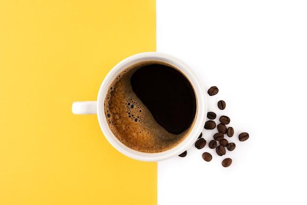 Heiße kaffeetasse auf gelbem und weißem hintergrund