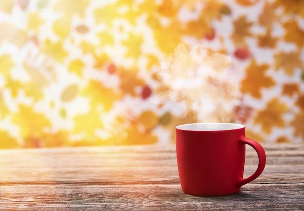Heiße kaffeetasse auf herbstlaub. rote kaffeetasse.