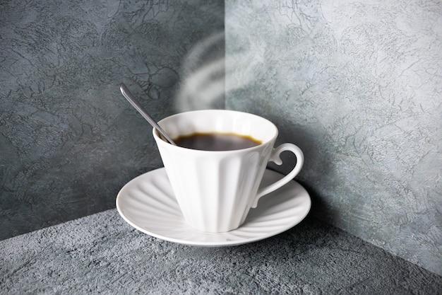 Heiße kaffeetasse aus weißem porzellan mit dampf, löffel und untertasse auf grauer oberfläche in der ecke.