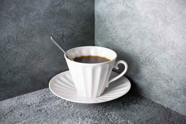 Heiße kaffeetasse aus weißem porzellan mit löffel und untertasse auf grauer oberfläche in der ecke.