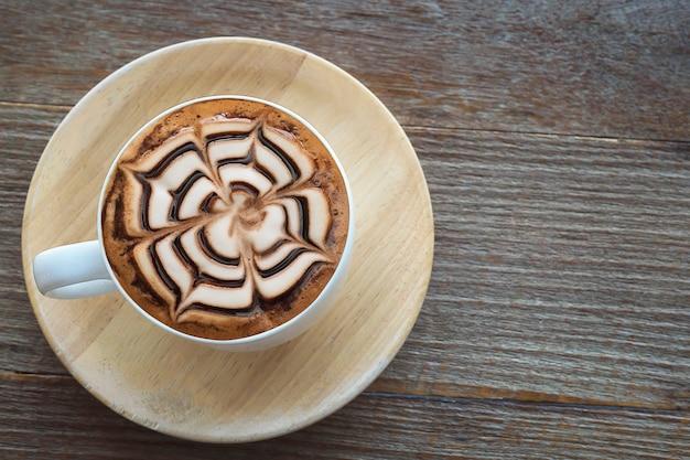 Heiße kaffeetasse der weinlese mit netter latte-kunstdekoration auf alter hölzerner beschaffenheitstabelle