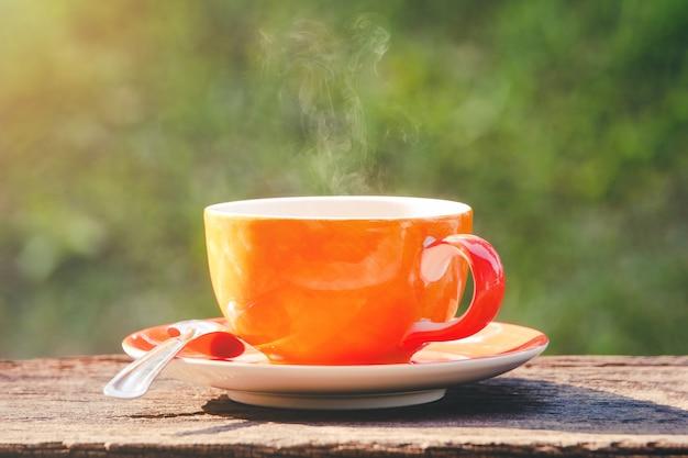 Heiße kaffeetasse erneuern morgenzeit auf natürlichem grünem hintergrund