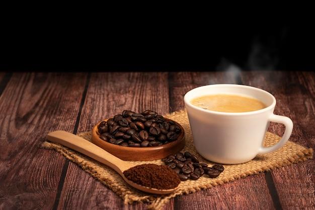 Heiße kaffeetasse mit bio-kaffeebohnen auf dem holztisch