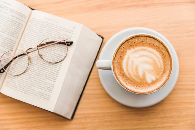 Heiße kaffeetasse mit cappuccino lattekunst und brillen über einem offenen buch auf tabelle