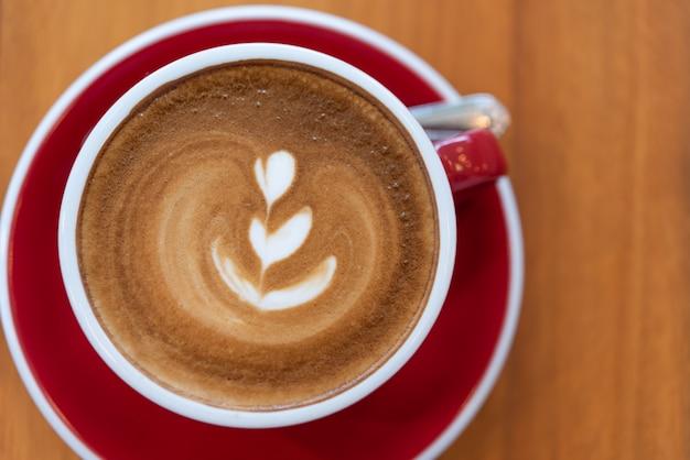 Heiße kaffeetasse mit lattekunst in der roten schale auf hölzernem hintergrund, ebenenlage