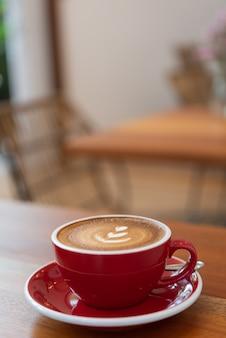 Heiße kaffeetasse mit lattekunst in der roten schale auf hölzerner tabelle im caférestaurant