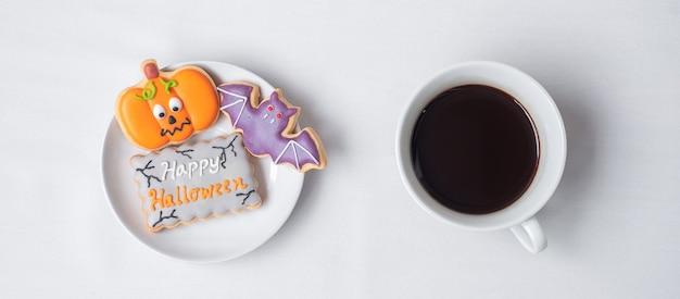 Heiße kaffeetasse mit lustigen halloween-plätzchen. fröhlicher halloween-tag, trick oder bedrohung, hallo oktober, herbstherbst, traditions-, party- und urlaubskonzept