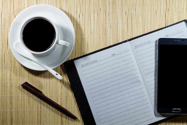 Heiße kaffeetasse mit notizbuch und mobile auf dem schreibtischgeschäftsmann