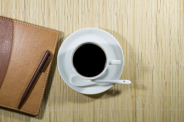 Heiße kaffeetasse mit notizbuch