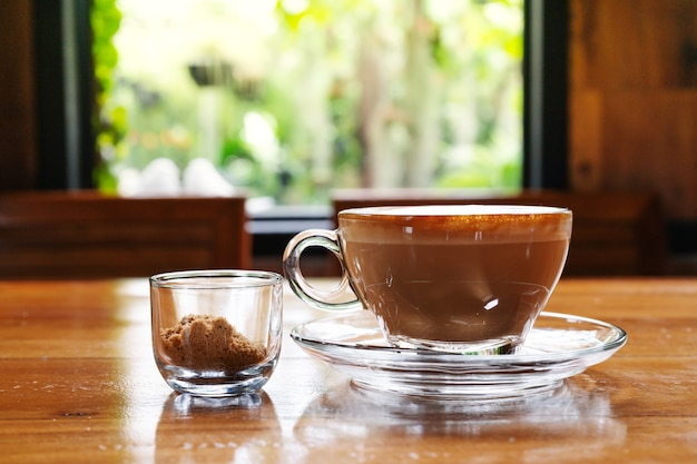 Heiße kaffeetasse mit rohrzuckerschale auf dem holztisch, fensteransicht