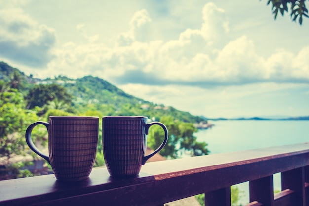 Heiße kaffeetasse mit schöner tropischer aussicht im freien