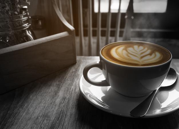 Heiße kaffeetasse mit warmem morgenlichtfenster