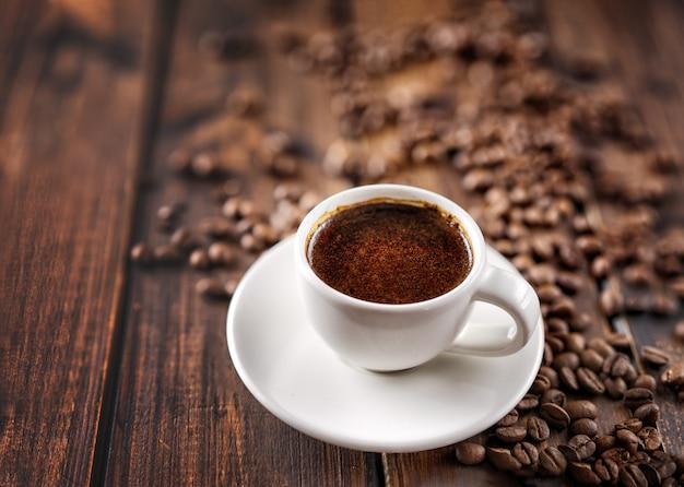 Heiße kaffeetasse und bohnen auf hölzerner tabelle