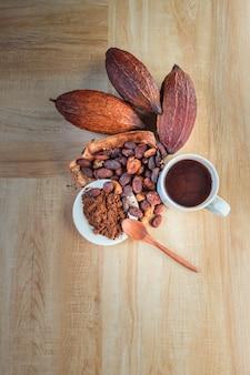 Heiße kakaotasse mit kakaopulver und kakaobohnen auf holztisch