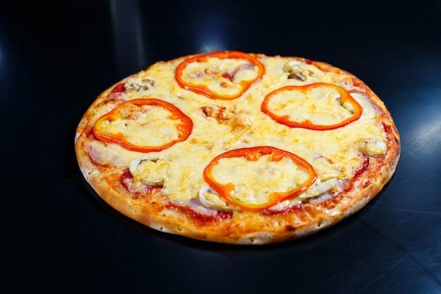 Heiße köstliche hausgemachte amerikanische pizza mit rotem pfeffer und fleisch mit einer dicken kruste auf einem schwarzen tisch
