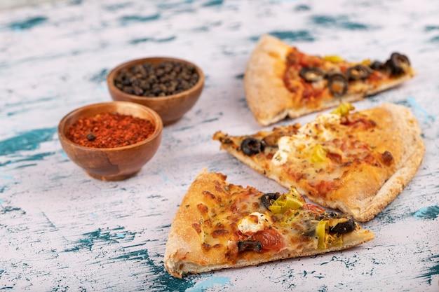 Heiße köstliche pizzastücke mit gewürzen, die auf einen steinhintergrund gelegt werden.