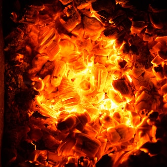 Heiße kohlen im feuer. abstrakter hintergrund der brennenden glut.