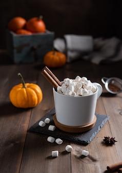 Heiße kürbis latte mit marshmallow, zimt und schokolade in einem weißen becher auf einem holztisch. dunkles und stimmungsvolles foto
