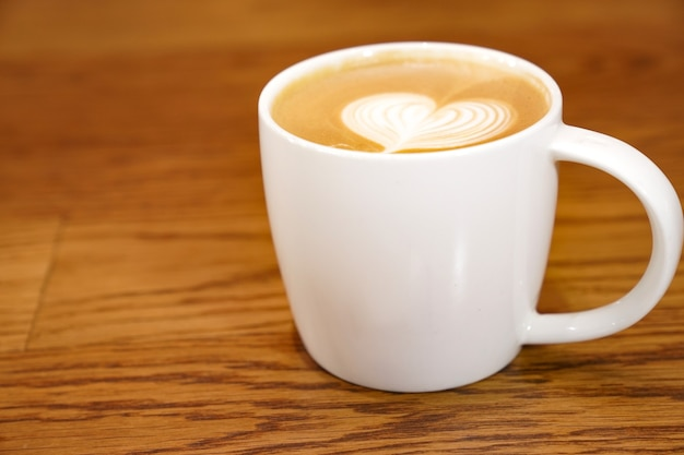 Heiße kunst latte in der weißen kunst auf dem holztisch